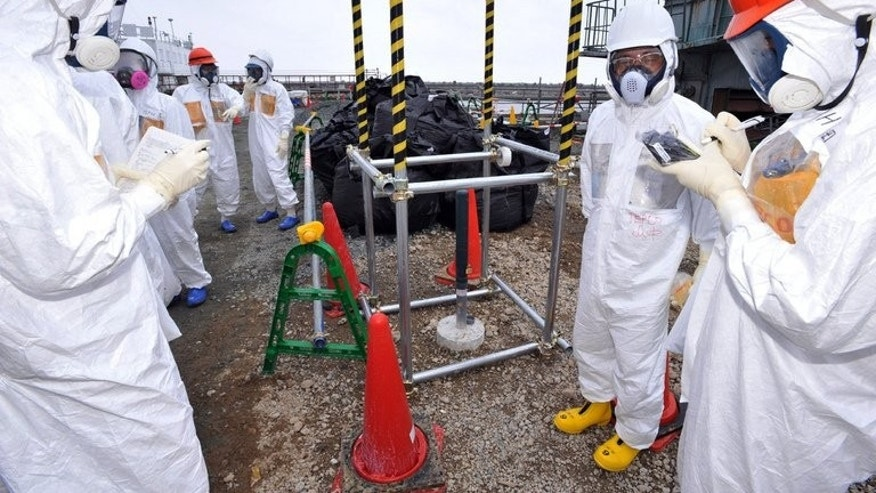 Nuclear experts and government officials inspect a monitoring well at Fukushima on August 6, 2013. Japan's PM Shinzo Abe is travelling to the Middle East in a bid to promote nuclear technology exports.