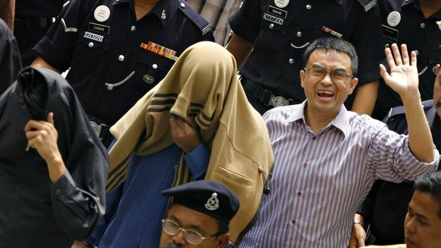 Abdul Razak Baginda (R) pictured with special unit police officers Sirul Azhar Umar (C) and Azilah Hadri (L) on, 29 June 2007. A murder conviction for the two officers was overturned Friday, while Abdul Razak was acquitted in 2008.
