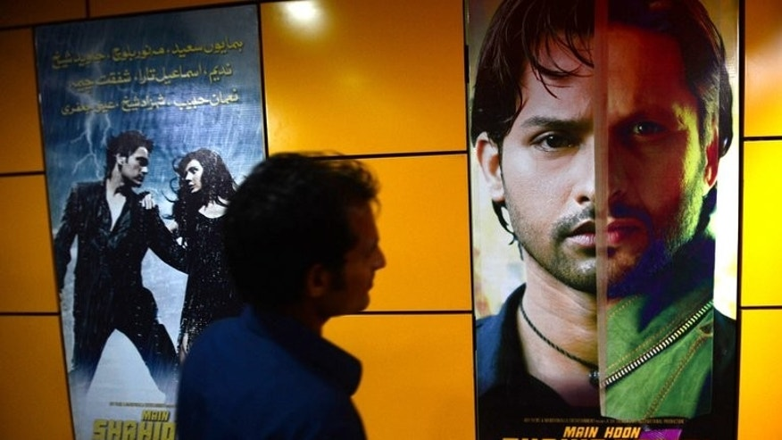 "A Pakistani customer looks at the poster of the film ""Main Houn Afridi"" (""I am Afridi"") at a cinema in Karachi on August 23, 2013. The Pakistani film about a boy emulating the fairytale career of cricket star Shahid Afridi hit cinemas Friday despite objections from the player over ""obscene"" scenes he fears could damage his image."