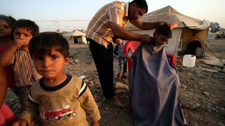 A Syrian-Kurdish man cutting the hair of a boy at the Quru Gusik refugee camp, 20 kilometres east of Arbil, the capital of the autonomous Kurdish region of northern Iraq, on August 22, 2013.