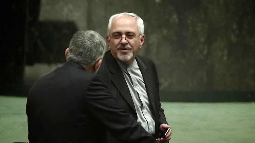 Mohammad Javad Zarif speaks with an MP in parliament in Tehran on August 15, 2013. The possession of a nuclear bomb would threaten Iran's security, the country's foreign minister, Mohammad Javad Zarif, said in comments reported on Friday.