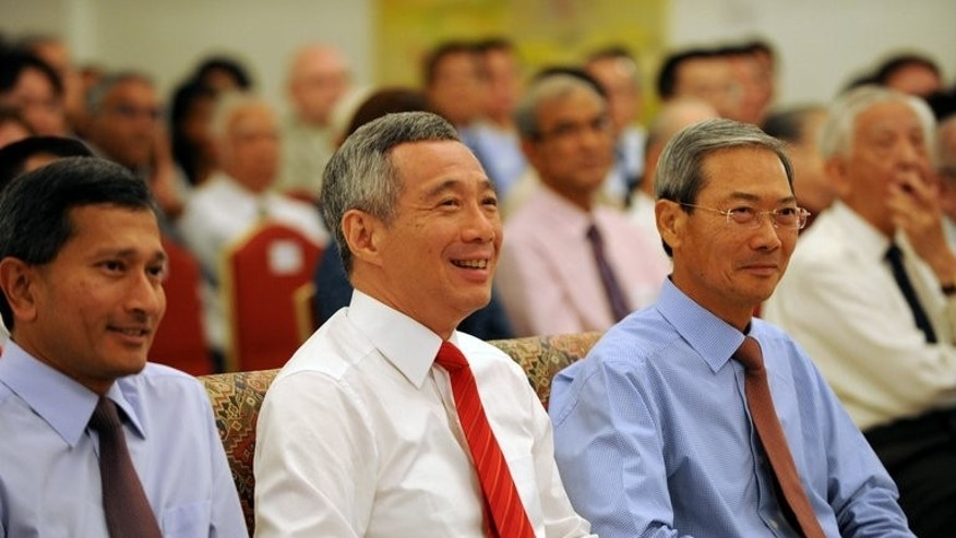 Singapore Prime Minister Lee Hsien Loong (centre) attends a book launch at the Istana Presidential Palace in Singapore on August 6, 2013. Singapore Prime Minister Lee Hsien Loong's efforts to connect with younger voters may finally pay off after a photo of him doing his first fist bump went viral on Facebook.