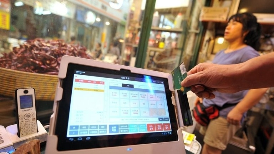 A manual cash register with a touchscreen tablet offered by SK Telecom is seen at a sesame oil store in Seoul's Junggok Cheil traditional market, on August 7, 2013. SK Telecom started to offer for free the new devices and necessary training to merchants early this year.
