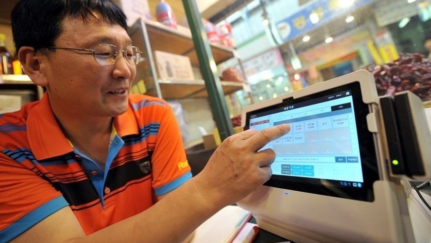 Yoo Hyung-Geun, sesame oil seller at Seoul's Junggok Cheil traditional market, demonstrates his manual cash register with a touchscreen tablet, offered by SK Telecom, on August 7, 2013. S.Korea's huge, family-run conglomerates have been blamed for stifling innovation and deliberately smothering small firms -- especially in the retail sector -- as they seek to expand into new markets.
