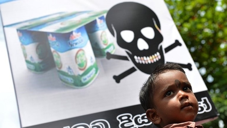 A Sri Lankan child looks on as pro-government activists protest the alleged contamination of milk powder outside the factory of dairy giant Fonterra in a Colombo suburb on August 22, 2013.