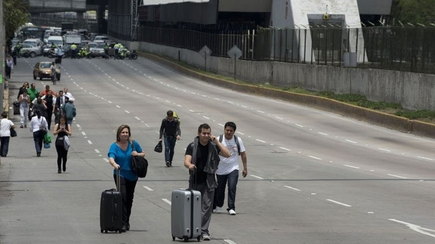 Passengers walk to Mexico City's Benito Juarez international airport as teachers block access highways to protest education reform legislation, on August 23, 2013.