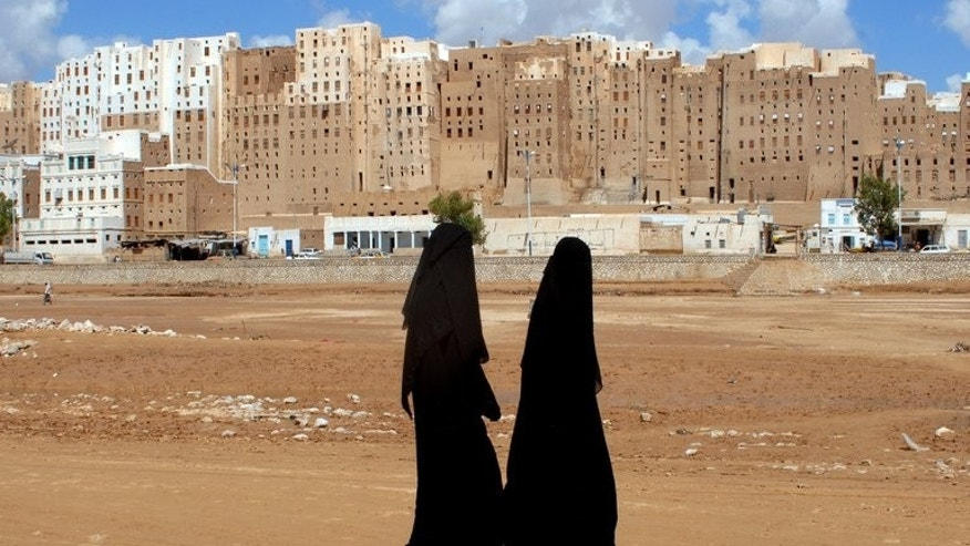 Yemeni women walk past the historical city of Shibam in Hadramaut province of eastern Yemen on October 28, 2008. A suicide bombing killed two soldiers and wounded six others in eastern Yemen on Friday, a military official said, blaming Al-Qaeda militants for the attack.