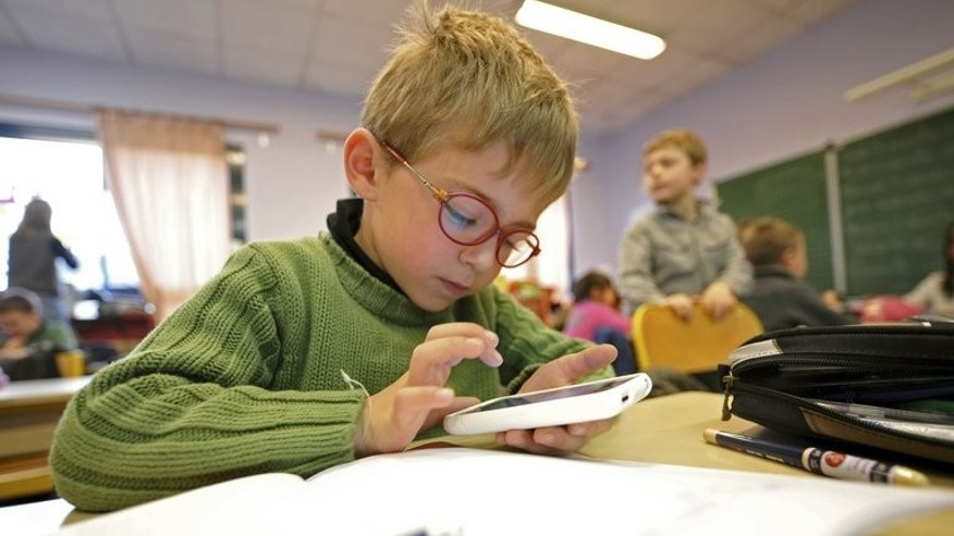 A boy writes on a smartphone during a lesson about Twitter in Seclin, France. The average British child receives his or her first mobile phone at the age of 11, but nearly one in ten has a phone by the time they are five, according to a new study.