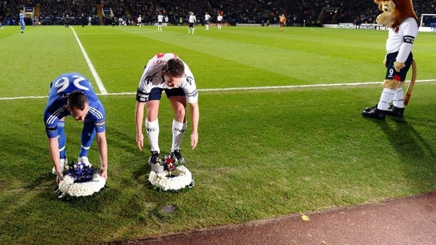 Bolton Wanderers mascot watches as Chelsea captain John Terry (left) and Bolton Wanderers captain Kevin Davies place wreaths by the side of the pitch following the death of former Bolton and England footballer Nat Lofthouse at The Reebok Stadium in Bolton on January 24, 2011. The club unveiled a statue of Lofthouse, the former England striker on Saturday.