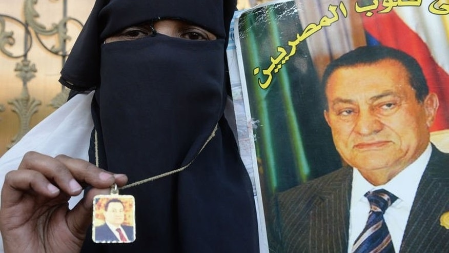 An Egyptian supporter of former president Hosni Mubarak displays portraits of him outside a military hospital where Mubarak was transferred after his release from prison on August 22, 2013 in Cairo. Mubarak returns to court Sunday to face charges over protester deaths, as Muslim Brotherhood leaders make their first appearances in court on similar but unrelated charges.