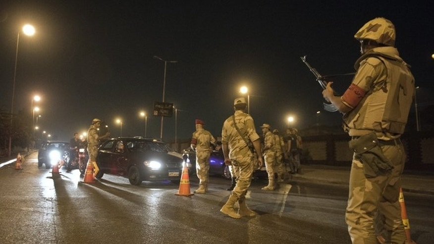 Egyptian troops stop cars at a checkpoint during the curfew hours in Cairo late on August 19, 2013. Egypt is to shorten its night-time curfew by two hours, pushing back the start time to 9:00 pm (1900 GMT) except on Fridays, the premier's office said on Saturday