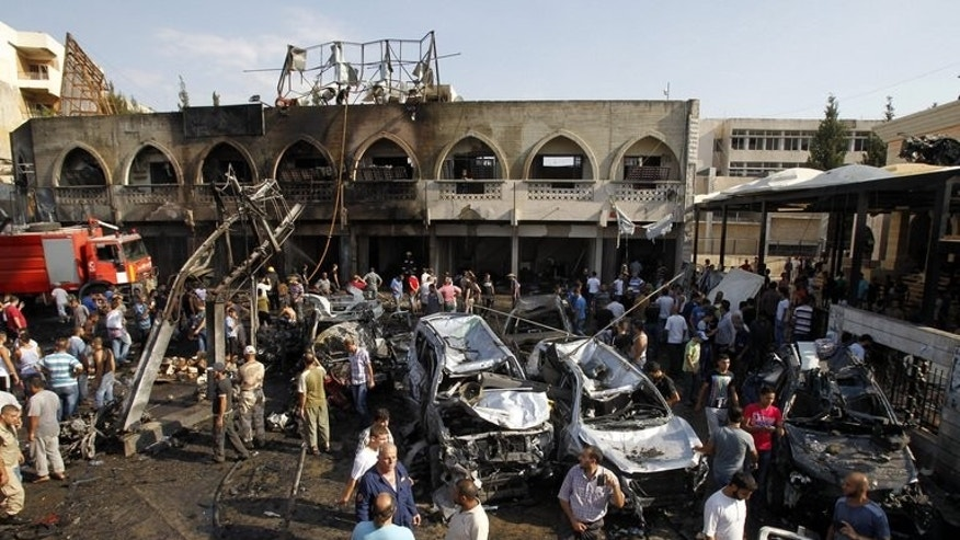 Lebanese civilians gather next to the site of a blast outside the Al-Taqwa mosque in the northern city of Tripoli on August 23, 2013. Lebanon is to observe a day of national mourning Saturday for 42 people killed in powerful bombings outside two Sunni mosques in a city riven by strife over Syria's war.