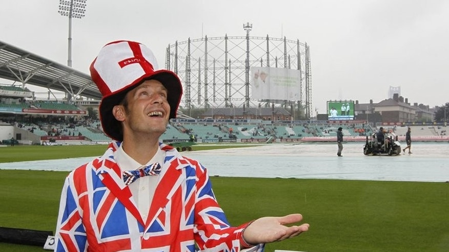 A spectator poses for a photograph after rain delays the start of the fourth day's play of the fifth Ashes cricket Test match between England and Australia at the Oval cricket ground in London on August 24, 2013.