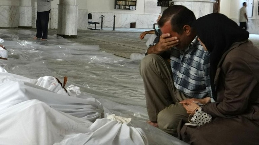 A handout image released by the Syrian opposition's Shaam News Network shows a Syrian couple mourning in front of bodies wrapped in shrouds ahead of funerals following what Syrian rebels claim to be a toxic gas attack by pro-government forces in eastern Ghouta, on the outskirts of Damascus on August 21, 2013.