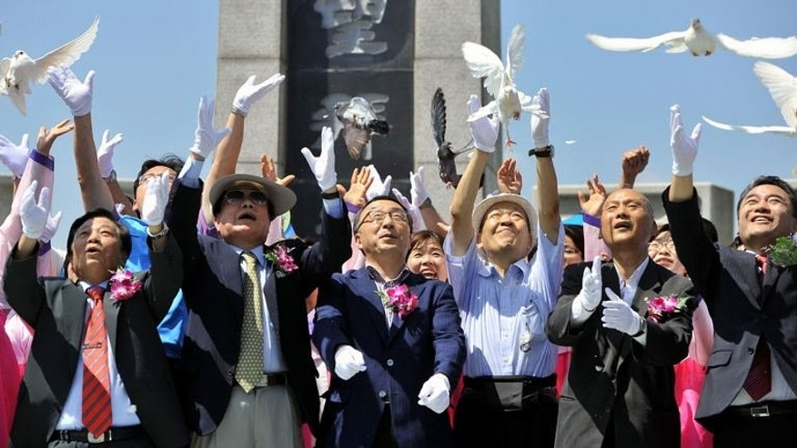 South Koreans release pigeons and pray for the unification of Korea near, in Paju, north of Seoul, on August 24, 2013. South Korea's Red Cross has announced a list of 500 potential candidates for reunions next month with their North Korean relatives separated for decades by the 1950-53 Korean War.