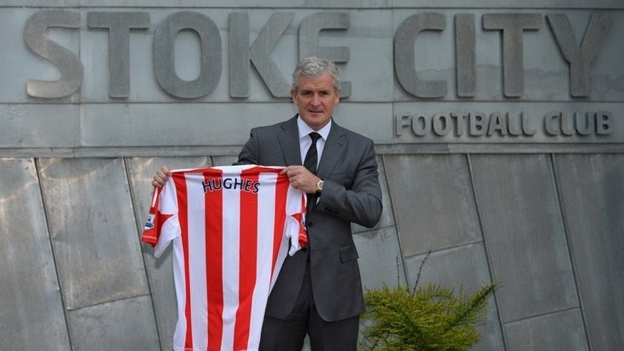 Mark Hughes holds up a Stoke City football shirt at the Stoke City training ground in Stoke-on-Trent, on May 30, 2013. Stoke City stormed back from behind to beat Premier League new boys Crystal Palace 2-1 on Saturday and earn manager Hughes victory in his first home game.