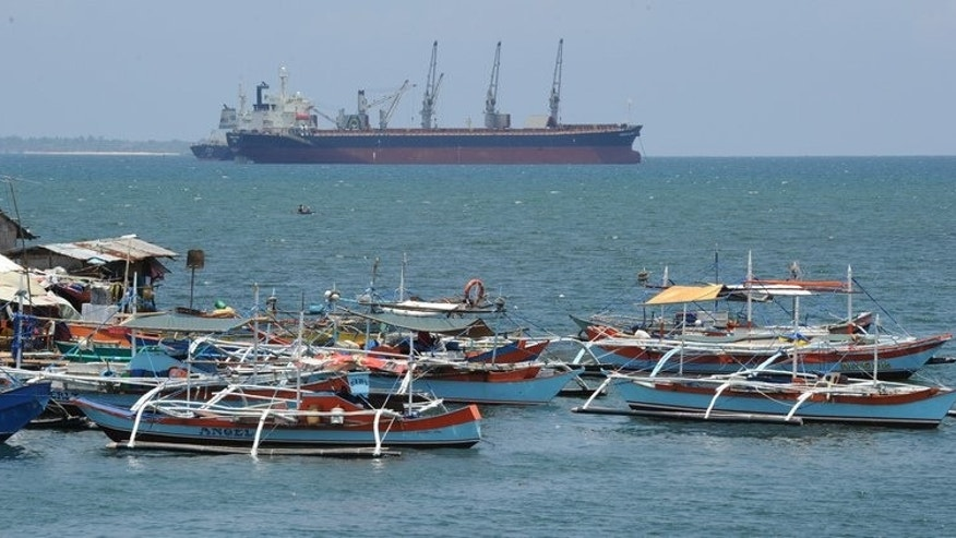 Philippine fishing boats are anchored near a foreign cargo vessel facing the South China sea at the port of Santa Cruz, Zambales province, north of Manila on May 10, 2012. The United States and the Philippines have vowed to maintain freedom of navigation in a Southeast Asia increasingly beset by maritime territorial rows, the two military allies said.