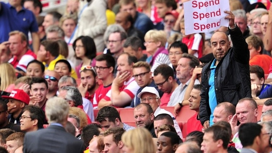"An Arsenal fan holds up a poster bearing the message ""spend, spend, spend"" for Arsenal's French manager Arsene Wenger (left) during the English Premier League football match with Aston Villa on August 17, 2013. The London club have had two bids for Uruguay international rejected Luis Suarez and the player has now been linked with a move to Real Madrid."