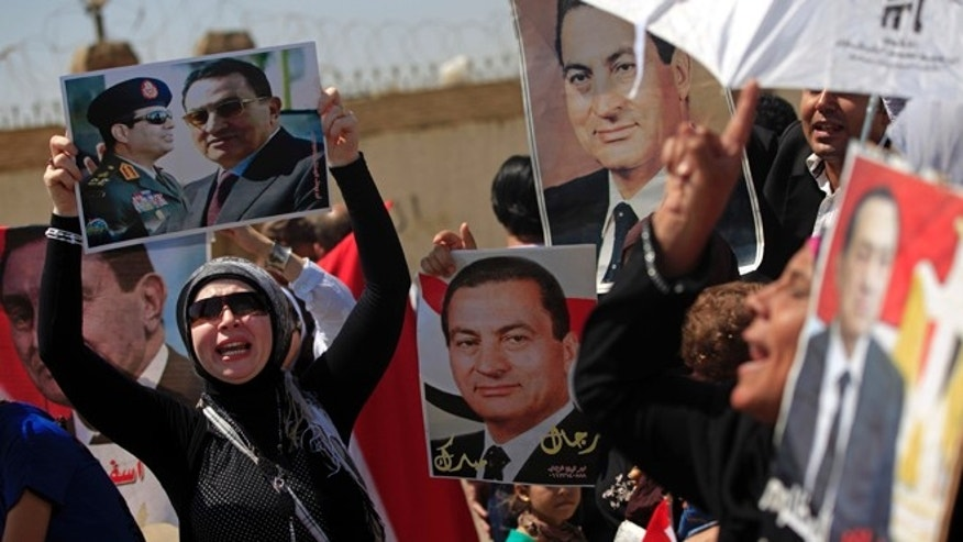 Aug. 25, 2013: Supporters of former Egyptian President Hosni Mubarak, hold posters of him as they protest outside the Cairo Police Academy turned court, Cairo, Egypt, Sunday. Mubarak, under house arrest after being released from detention last week, is standing retrial in charges of complicity in the killings of protesters during 2011 Egyptian uprising.