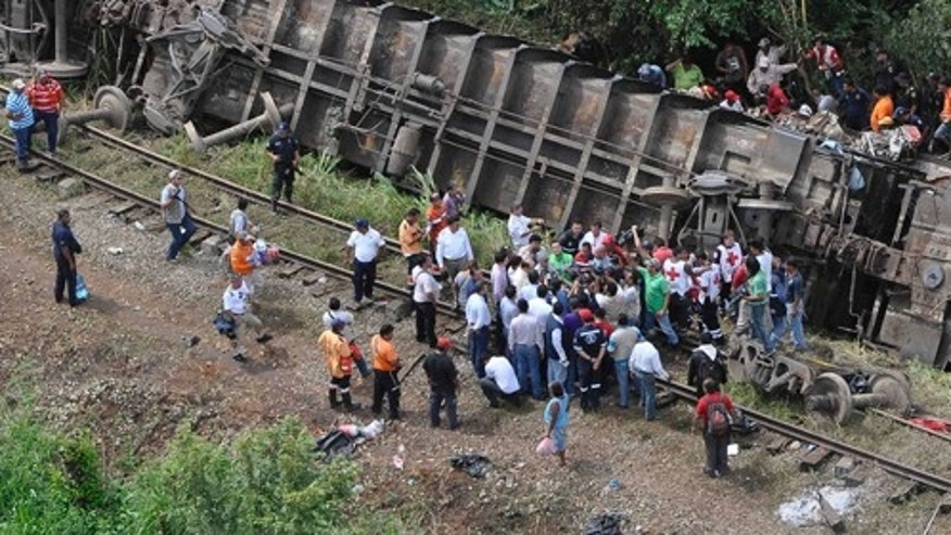 """In this image released by the Tabasco state government press office on Sunday Aug. 25, 2013, rescue workers try to evacuate the injured after a cargo train, known as """"the Beast"""", derailed near the town of Huimanguillo, southern Mexico. The cargo train, carrying at least 250 Central American hitchhiking migrants derailed in a remote region, killing at least five people and injuring dozens, authorities said. (AP Photo/Tabasco state government press office)"""