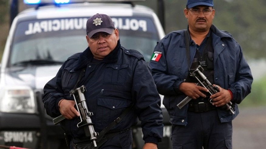 Aug 22, 2013: Municipal police guard the entrance to Rancho La Mesa where a mass grave was found in the municipality of Tlalmanalco, Mexico.