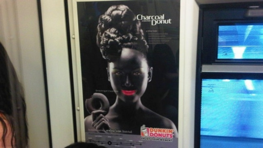 Aug. 30, 2013: An advertisement poster of a smiling woman with bright pink lips in blackface makeup holding a doughnut is seen on a Skytrain, a commuter train in Bangkok, Thailand.