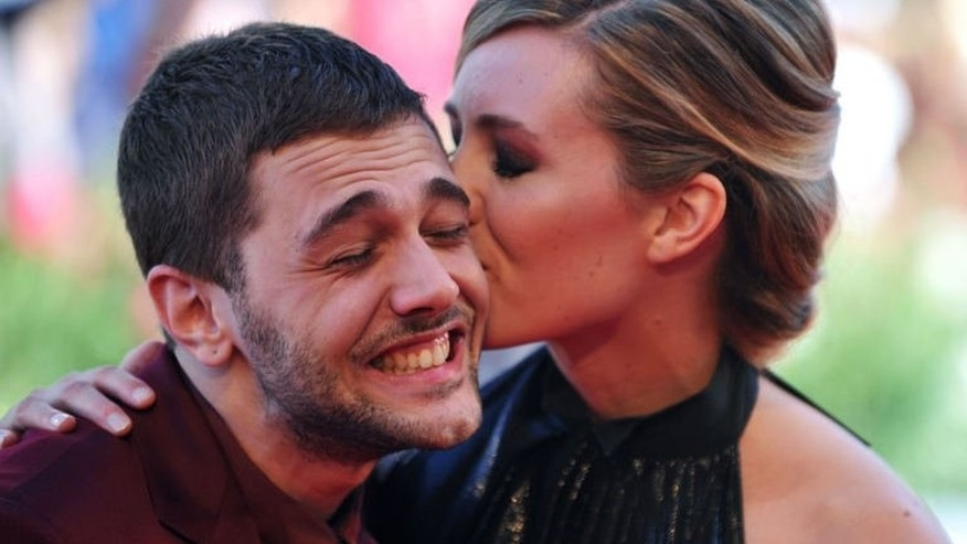 """Actress Evelyne Brochu kisses Canadian director Xavier Dolan as they arrive for the screening of """"Tom a la Ferme"""" presented in competition at the 70th Venice Film Festival on September 2, 2013."""