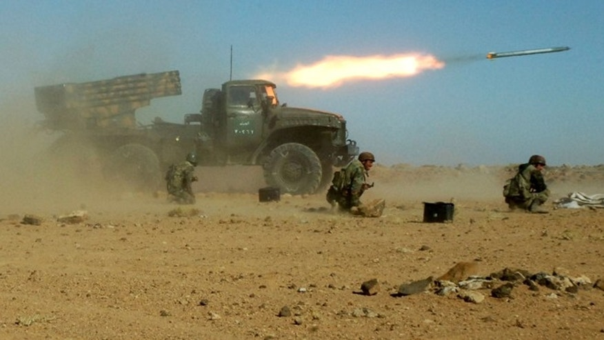This Sunday, Dec. 4, 2011 photo provided by the Syrian official news agency SANA, shows Syrian soldiers kneeling next to a multiple rocket launcher as they fire missiles during a maneuver at an unknown location, in Syria. As the Obama administration tries to prod Congress into backing armed action against Syria, the regime in Damascus is hiding military hardware and shifting troops out of bases into civilian areas.
