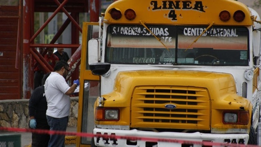 "August 29, 2013: Forensic workers examine the scene where a bus driver was allegedly killed by a self-styled ""bus driver hunter,"" in Ciudad Juarez, Mexico."