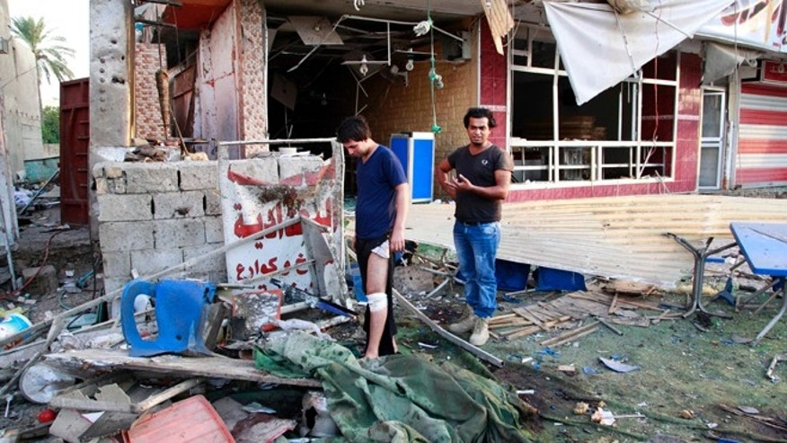 Sept. 4, 2013: People inspect the site of a car bomb attack at the Karrada neighborhood of Baghdad, Iraq. A series of coordinated evening blasts in Baghdad and other violence killed and wounded scores of people on Tuesday, officials said, the latest in a months-long surge of bloodshed that Iraqi security forces are struggling to contain.