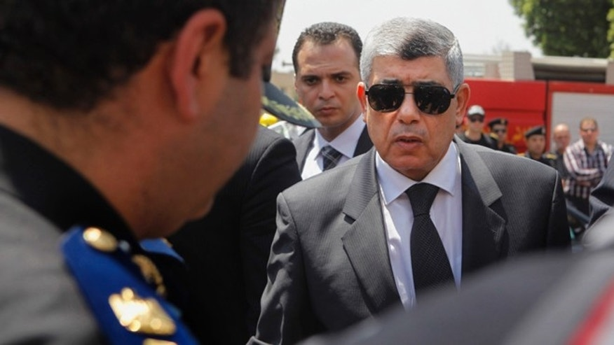 Aug. 15, 2013: In this file photo, Egyptian Interior Minister Mohammed Ibrahim, right, gives his condolences to a policeman during a military funeral in Cairo, Egypt. An explosion on Thursday, Sept. 5, 2013, targeted the convoy of the interior minister in Cairo's eastern Nasr City district, security officials and state television said. Ibrahim survived the attack.