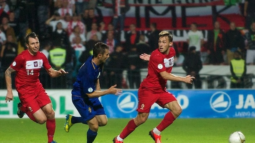 Moldova's Alexandru Antoniuc (C) fights for the ball with Poland's Sebastian Boenisch (R) and Jakub Wawrzyniak during their 2014 FIFA World Cup qualifier, at Zimbru Stadium in Chisinau, on June 7, 2013. Moldova travel to England next, on Friday.