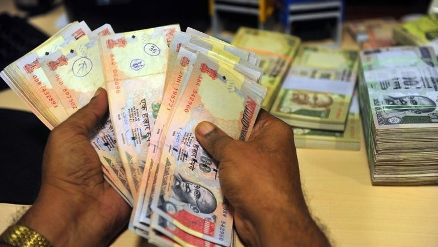 An Indian employee looks for illegal rupee currency notes at a bank in Mumbai on September 3, 2013. India's rupee strengthened and stocks jumped after new central bank governor Raghuram Rajan outlined a reform plan aimed at boosting investor confidence and stabilising the ailing currency.