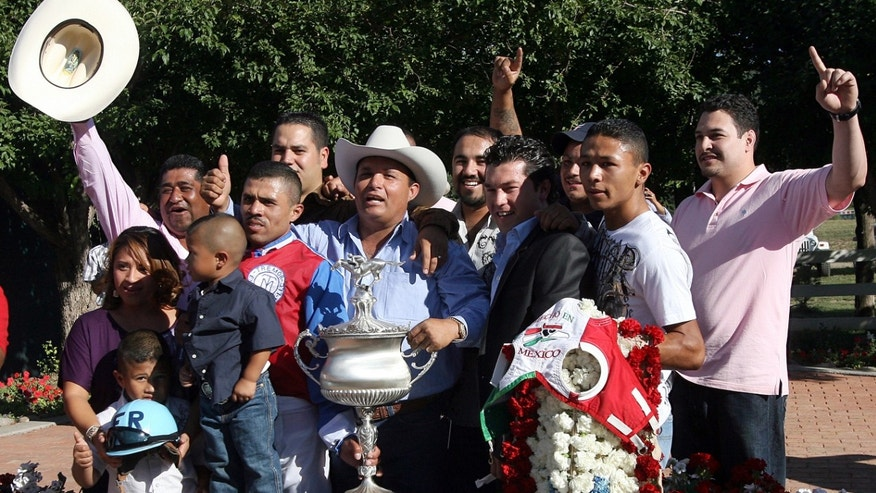 Jose Trevino Morales, center, acknowledges the crowd in 2010 after Mr. Piloto won the All-American Futurity horse race at Ruidoso Downs, N.M.