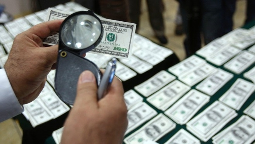 FILE - In this Aug. 17, 2012 file photo, a police officer inspects an alleged counterfeit $100 U.S. dollar note during a media presentation in Lima, Peru. With its meticulous criminal craftsmen, cheap labor and, by some accounts, less effective law enforcement, Peru has in the past two years overtaken Colombia as the No. 1 source of counterfeit U.S. dollars, says the U.S. Secret Service, protector of the worldâs most widely-traded currency. (AP Photo/Karel Navarro, File)