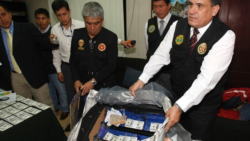FILE - In this Aug. 17, 2012 file photo, a police officer shows counterfeit $100 U.S. dollar notes during a media presentation in Lima, Peru. The Andean country became more attractive to counterfeiters as Washingtonâs decade-long Plan Colombia program tightened the screws not just on drug traffickers in the neighboring nation but other criminals as well. Counterfeiting in Peru, meanwhile, got better. Counterfeiters earn up to $20,000 in real currency for every $100,000 in false bills they produce after expenses. (AP Photo/Karel Navarro, File)