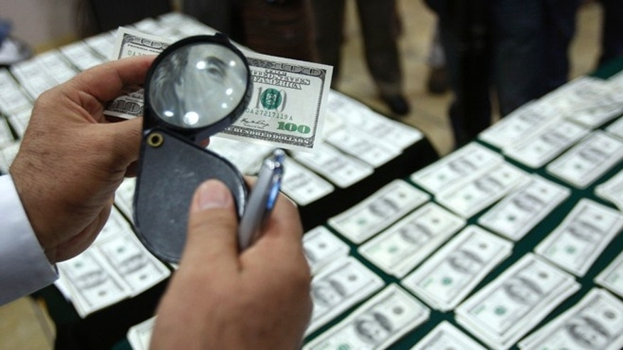 In this Aug. 17, 2012 file photo, a police officer inspects an alleged counterfeit $100 U.S. dollar note during a media presentation in Lima, Peru. With its meticulous criminal craftsmen, cheap labor and, by some accounts, less effective law enforcement, Peru has in the past two years overtaken Colombia as the No. 1 source of counterfeit U.S. dollars, says the U.S. Secret Service, protector of the worlds most widely-traded currency.