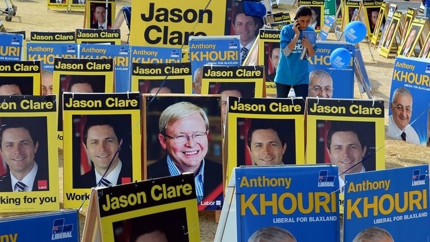 Portriats of the election contestants are seen in front of a pre-poll voting centre in Sydney, on September 6, 2013. Australian Prime Minister Kevin Rudd refused to concede defeat despite a new poll showing he is heading for an election wipe-out as the media swung behind rival Tony Abbott.