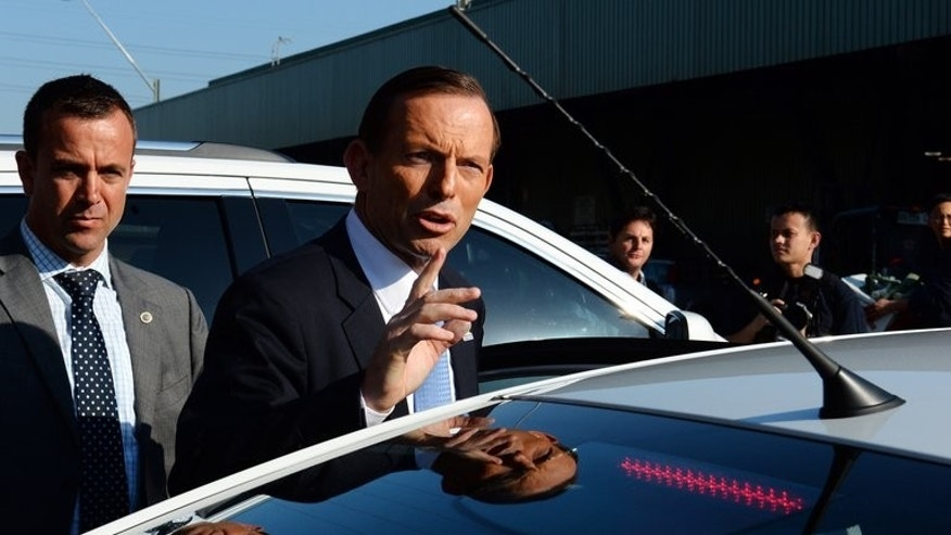 Australia's oppostion leader Tony Abbott (C), seen after visiting Flemington Sydney Market, on September 4, 2013. The man tipped to become Australia's next prime minister has ditched his 'Mad Monk' tag and softened his macho image to turn around his conservative party's fortunes ahead of September 7 election.