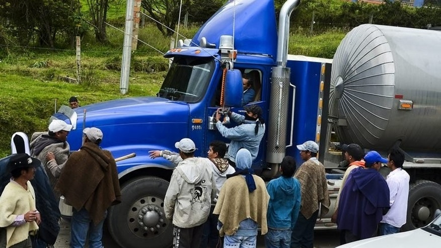 Colombian farmworkers stop a truck as they block the Bogota-Tunja highway, in Ventaquemada, Colombia, on August 20, 2013, to push their demands for aid to compensate for cheaper imports from the US under a free trade accord. Faced with social unrest and with only a few weeks left in which to decided whether to run for another term, President Juan Manuel Santos has reshuffled his cabinet.