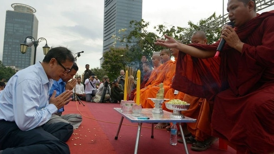 Leader of the opposition Cambodia National Rescue Party Sam Rainsy (L) prays before Buddhist monks in Phnom Penh on September 4, 2013.