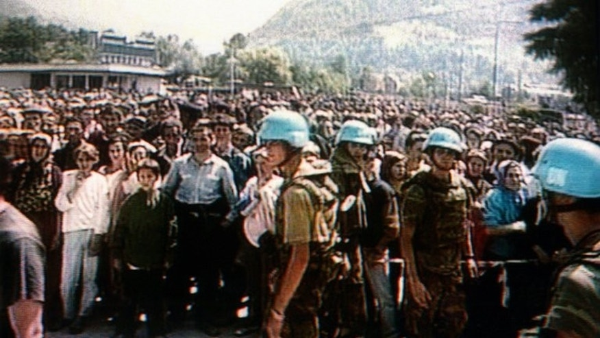 Photo taken on July 12, 1995 from the Dutch TV channel NOS shows Dutch soldiers standing in front of hundreds of Bosnian Muslim refugees in Potocari, the UN compound near Srebrenica.