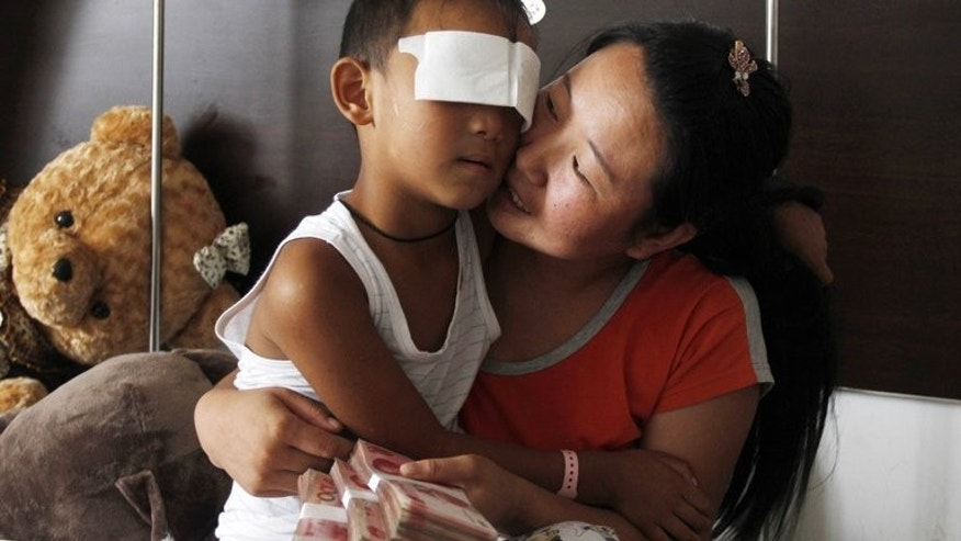 Six-year-old boy, Guo Bin, known as Bin-Bin, who was blinded when his eyes were gouged out after he went missing while playing outside on August 24, is being hugged by his mother at a hospital in Taiyuan, north China's Shanxi province, on September 3, 2013. She holds donations from well wishers.
