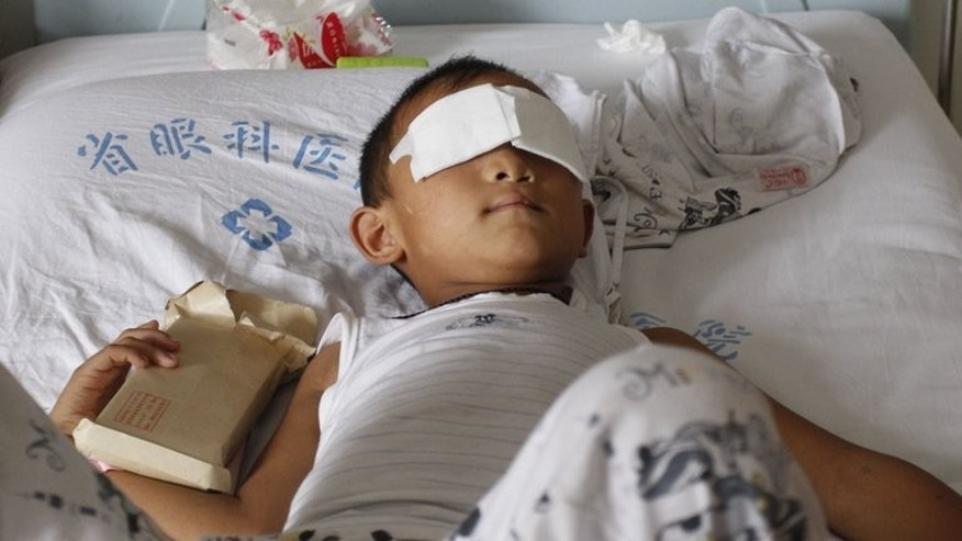 Six-year-old Guo Bin, known as Bin-Bin, pictured as he holds money donated by well-wishers while resting on his hospital bed in Taiyuan, north China's Shanxi province, on September 3, 2013. Bin-Bin had his eyes gouged out by a woman believed to be his aunt.
