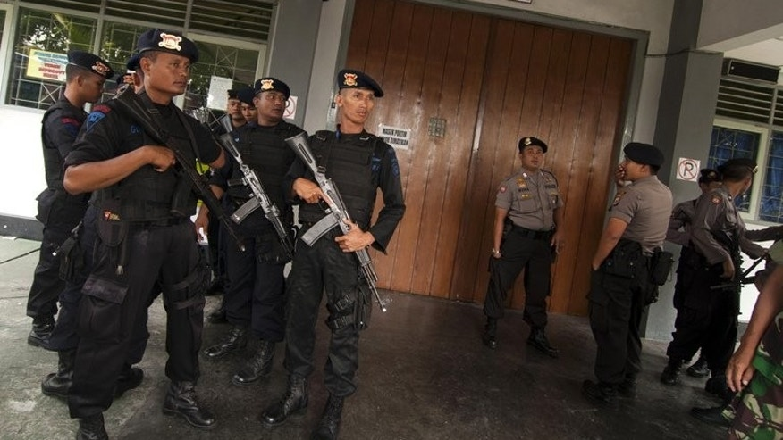 In this file photo, armed police stand guard after a shooting inside the Cebongan Correctional Centre in Yogyakarta, on March 23, 2013. Those killed in the attack were in custody accused of murdering one of the soldiers' superior officers in a nightclub brawl.