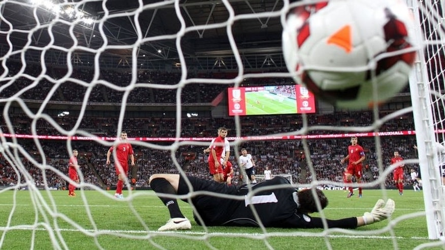 Moldova's goalkeeper Stanislav Namasco dives for the ball as England's Steven Gerrard scores the opening goal in London, on September 6, 2013.