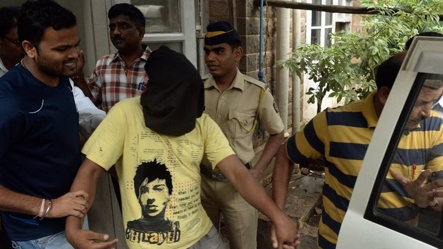 Indian police escort a suspect in the gang-rape of a photographer from a court in Mumbai,on August 25, 2013. Three of the men accused of gang-raping a photographer in Mumbai allegedly raped a teenager in the same spot just weeks earlier, according to police.