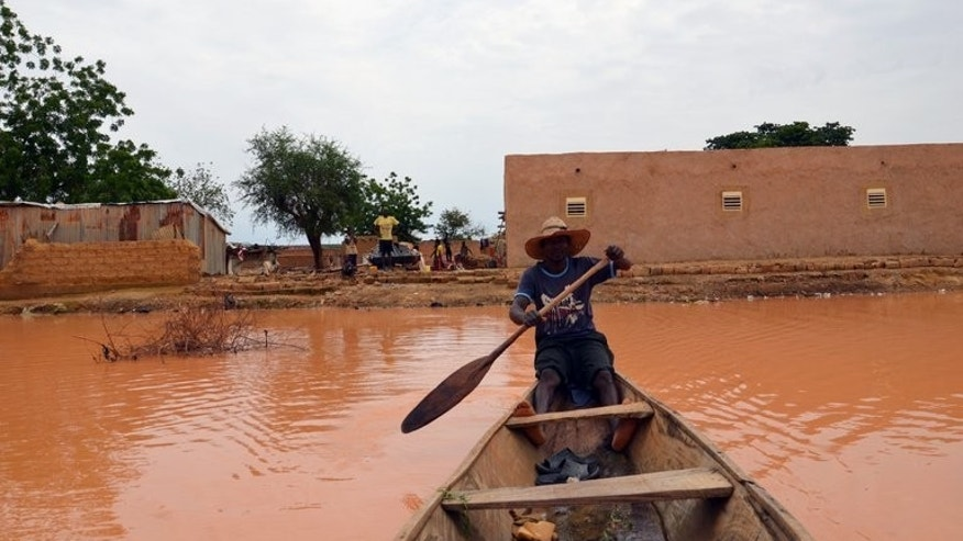 "A man rows through floods waters on September 5, 2013 in Niamey, Niger. Niger's government has launched an appeal for ""international solidarity"" to help victims of recent floods that claimed more than two dozen lives and forced 75,000 people from their homes."