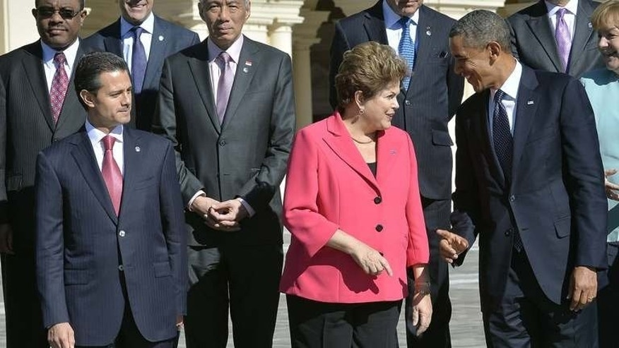 US President Barack Obama (R) talks to Brazil's President Dilma Rousseff (C) as Mexico???s President Enrique Pena Nieto looks on, at the G20 summit on September 6, 2013 in Saint Petersburg. Obama moved to defuse a row with Brazil and Mexico over alleged US spying on leaders of the Latin American countries.