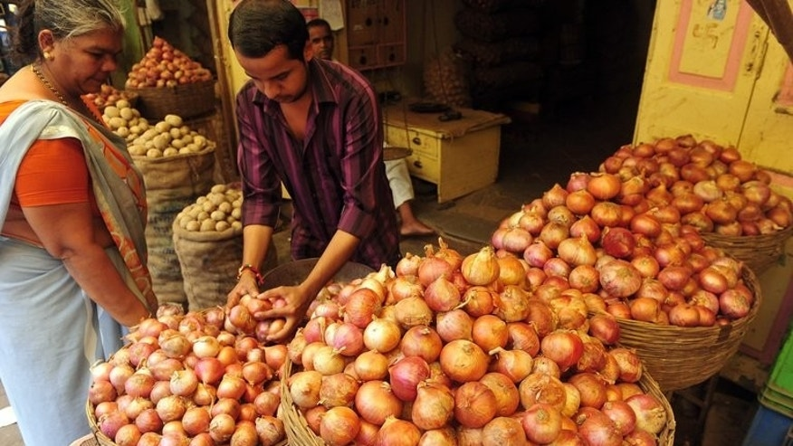 "A customer looks on as a shop assistant selects onions for her at a market in Mumbai on August 22, 2013. A US-based website offering onions at heavily discounted prices in India has seen an ""overwhelming"" response as consumers there reel from sky-rocketing prices of the vegetable."